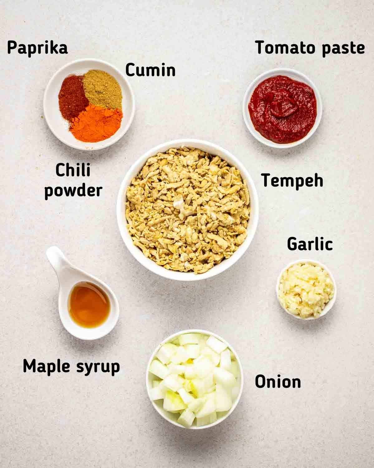 Ingredients needed like tempeh, garlic, onion, spices, tomato paste and maple syrup.