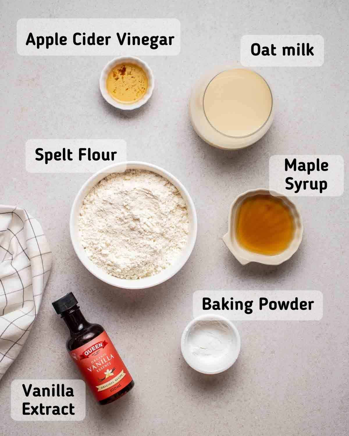 Ingredients needed for pancakes like flour, vinegar, oat milk, syrup, baking powder and vanilla extract on grey background.