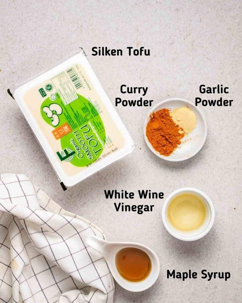Ingredients needed to make dressinglike silken tofu, curry powder, garlic powder, vinegar and maple syrup on grey background.