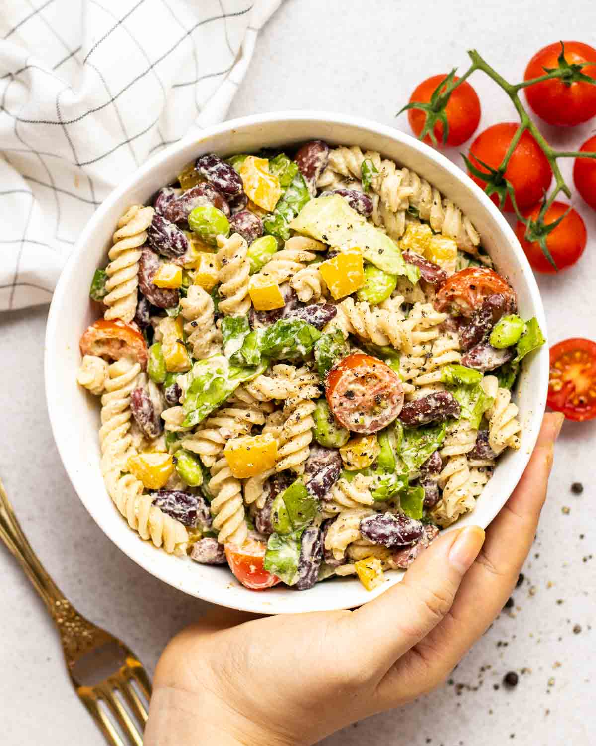 A hand holding a bowl of pasta salad.