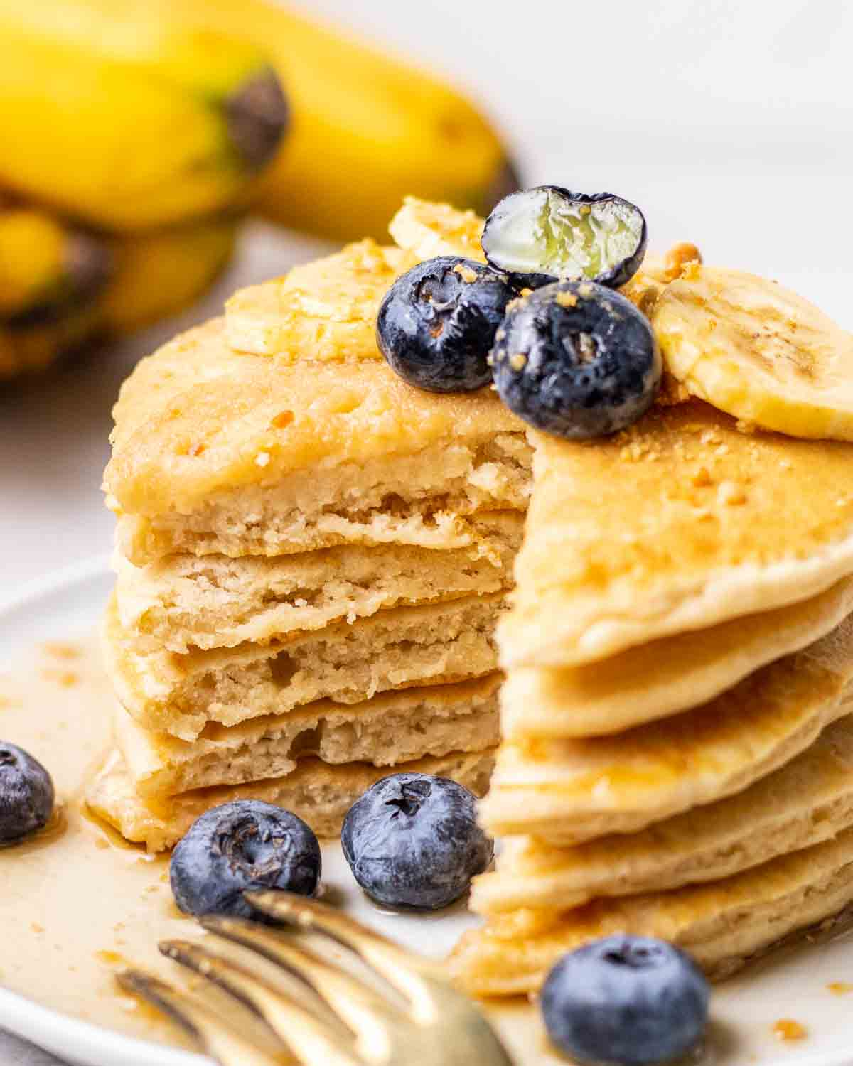 Stack of pancakes with triangular wedge cut through them with a fork beside.