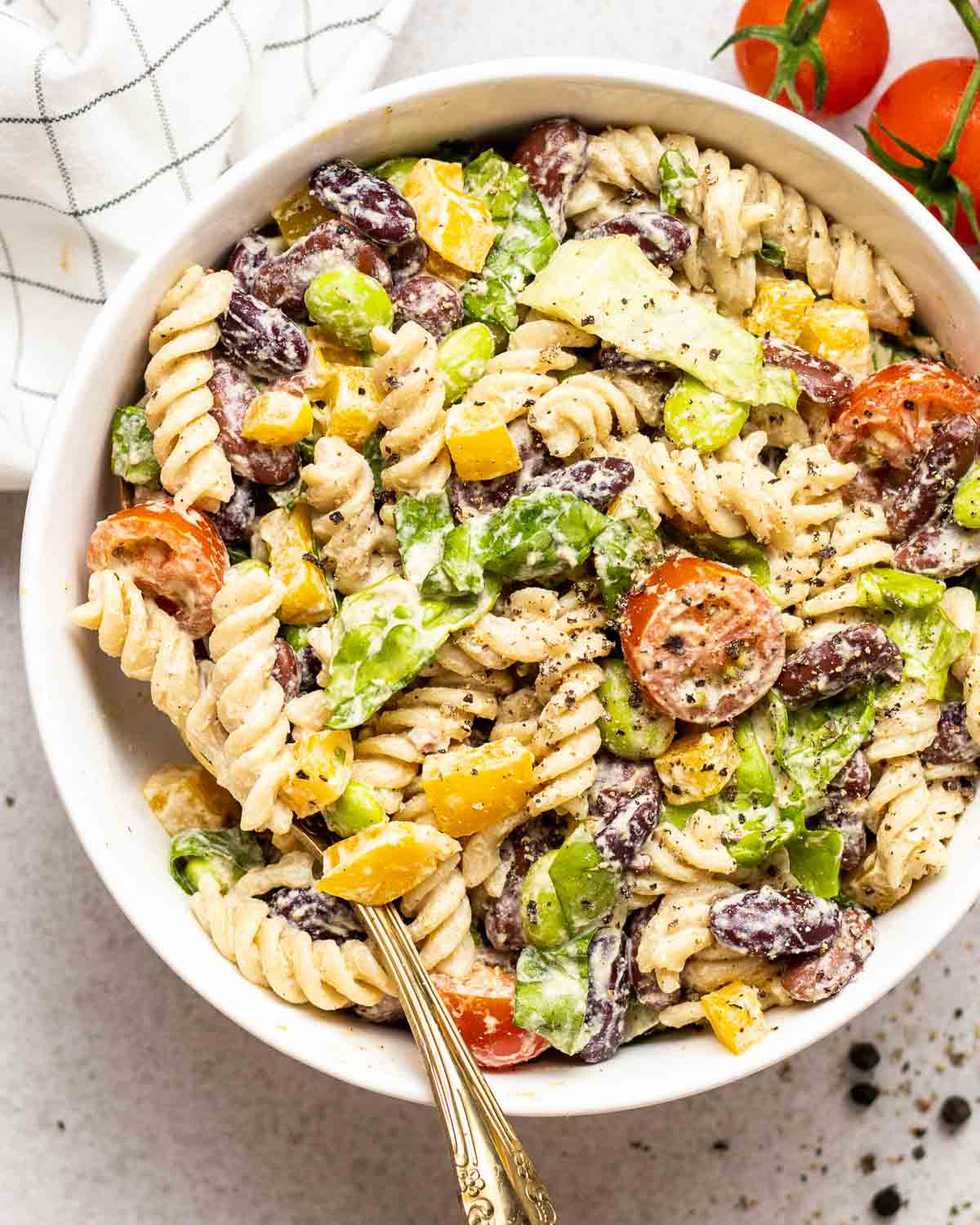 Pasta salad in a white bowl topped with black pepper with a fork.