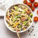 Pasta salad in a white bowl with fork. There are cherry tomatoes and black peppercorns in the background.