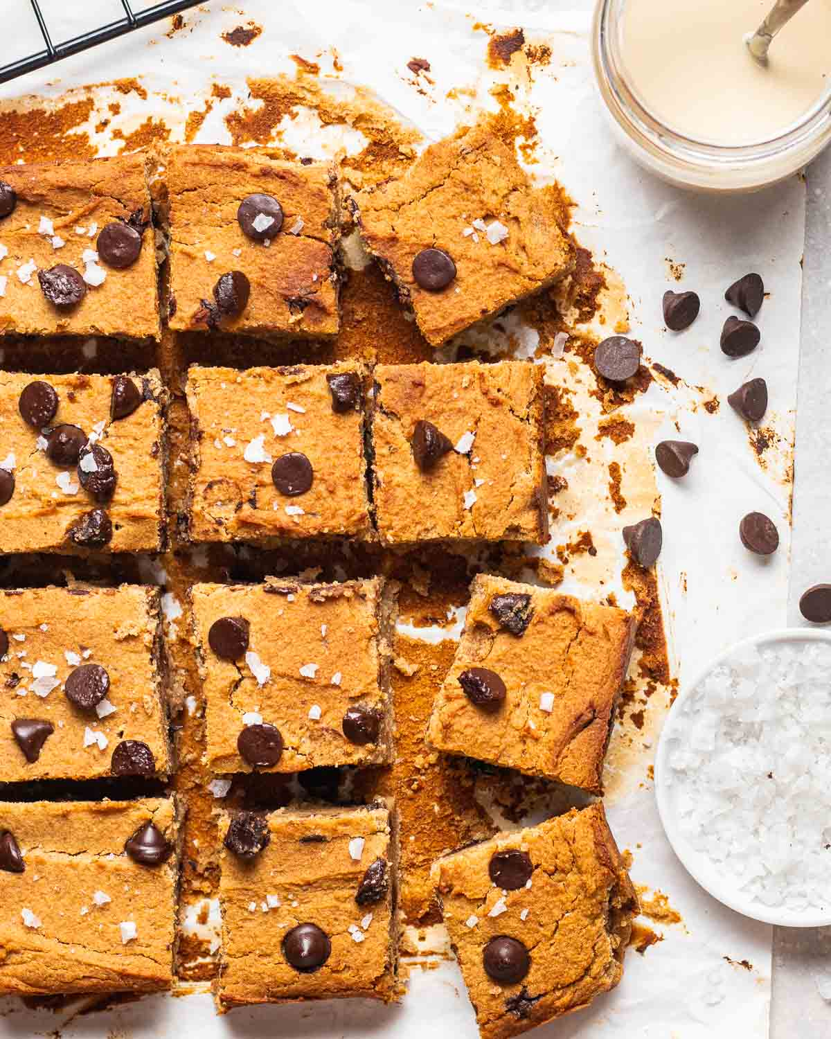 A tray of sliced blondies on a parchment paper with tahini, chocolate chips and salt in the background.
