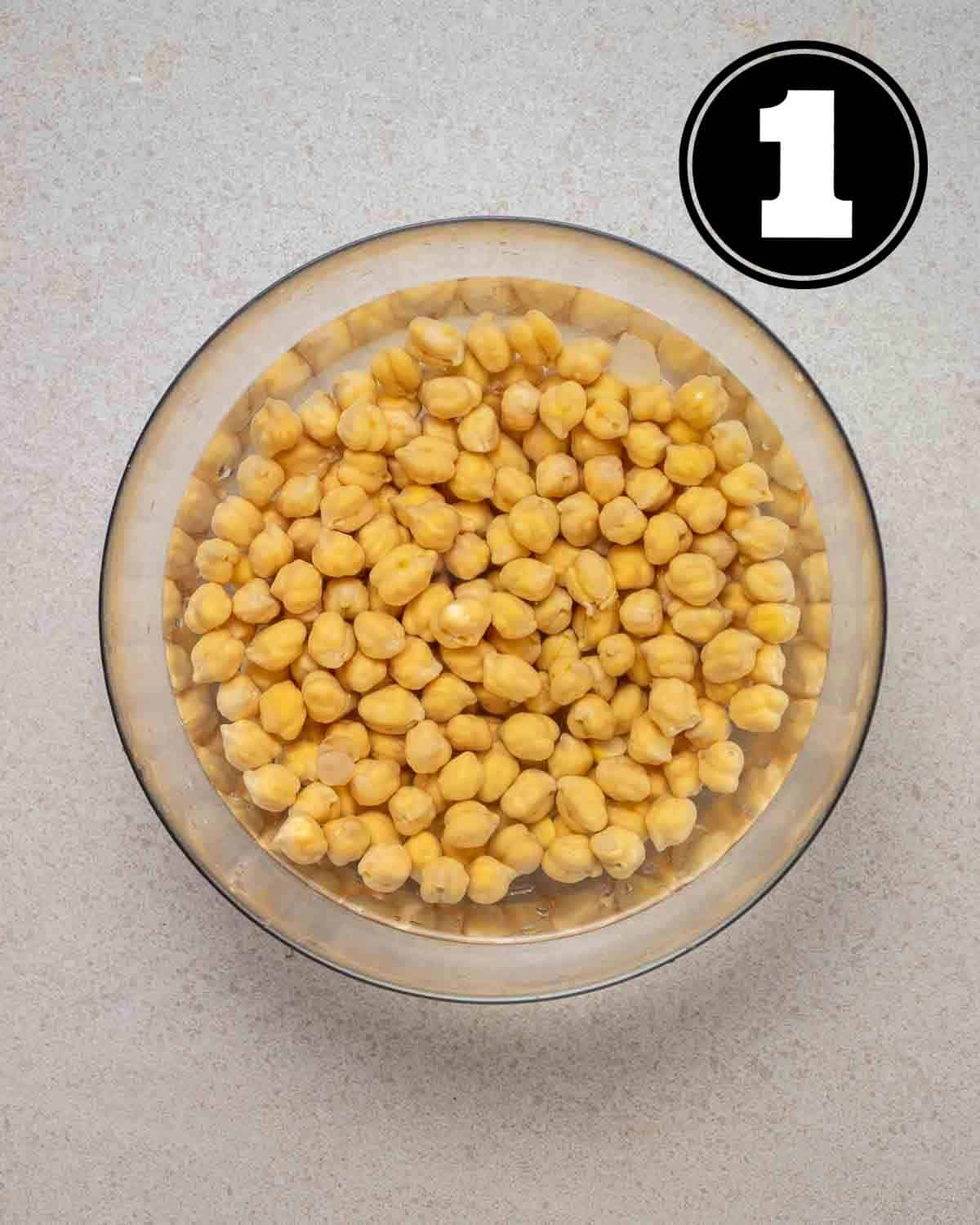 Soaking chickpeas in water in a glass bowl.