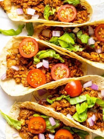 A few tacos arranged on a parchment paper.