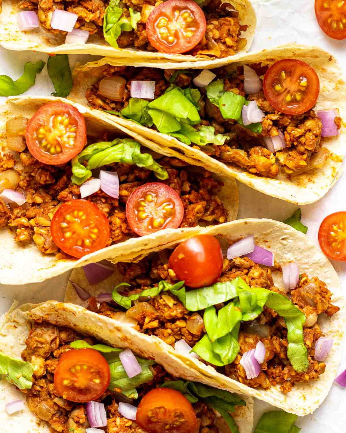5 tacos filled with halved cherry tomatoes, shredded lettuce and taco meat.