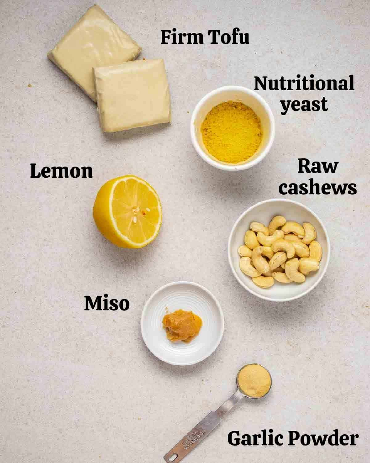 Ingredients needed for vegan ricotta like tofu, cashews, nutritional yeast and lemon on a grey background.