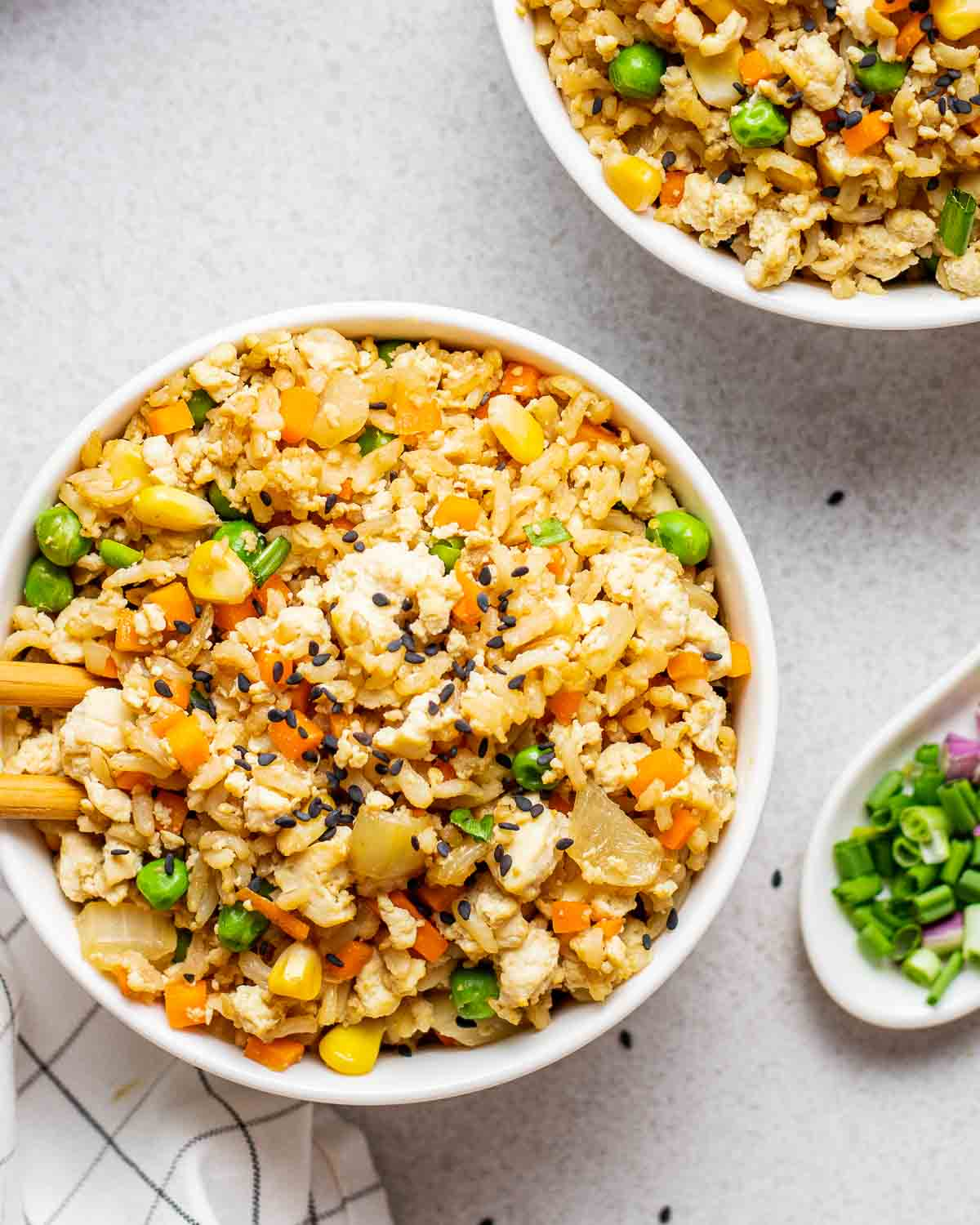Fried rice in a bowl with chopsticks. There is another bowl of fried rice and chopped scallions in the background.