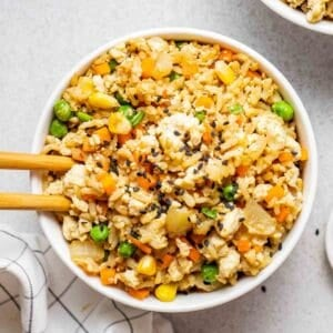 Tofu fried rice in a white bowl with chopsticks.