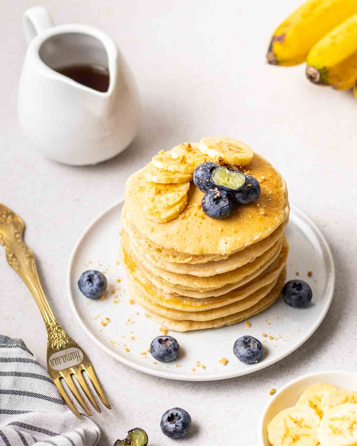 A stack of pancakes topped with banana and blueberries with a fork, jug if maple syrup and banana beside.