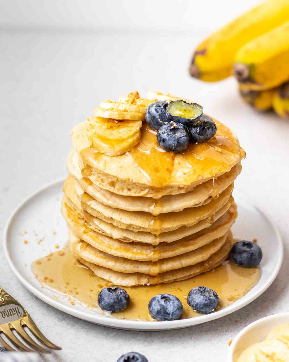Maple syrup dripping off a stack of pancakes in a blue plate with a bunch of bananas in the background.