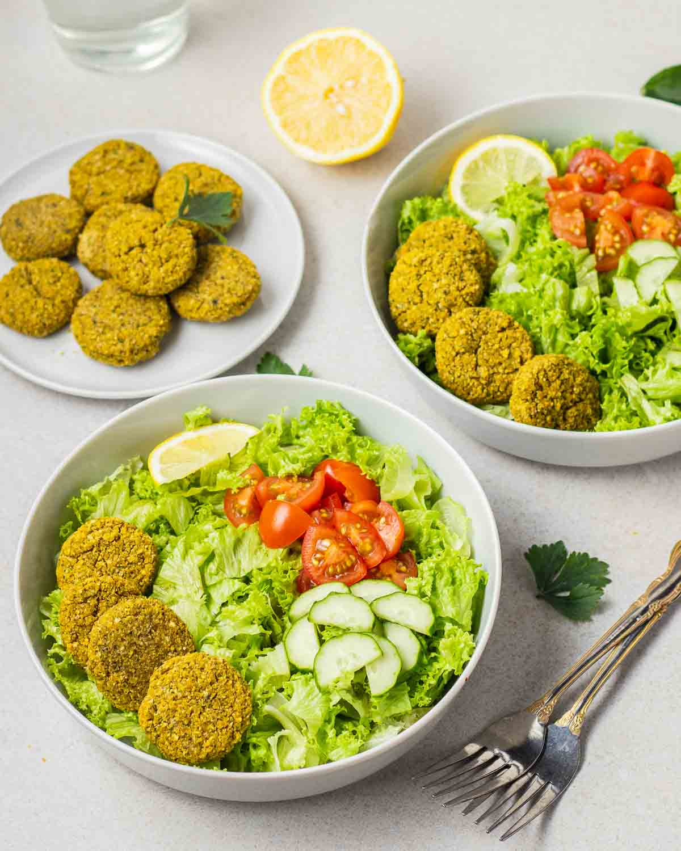 2 bowls of falafel salad with a plate of falafels, forks and half a lemon in the background.