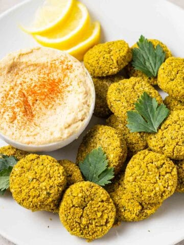 Falafels in a white plate topped with parsley leaves and served with hummus and lemon slices.