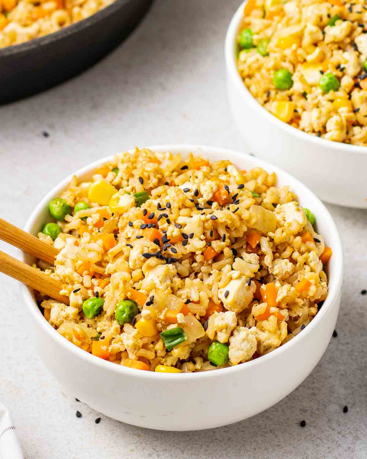 Fried rice in a white bowl with a pair of chopsticks. There is another bowl of rice and skillet in the background.