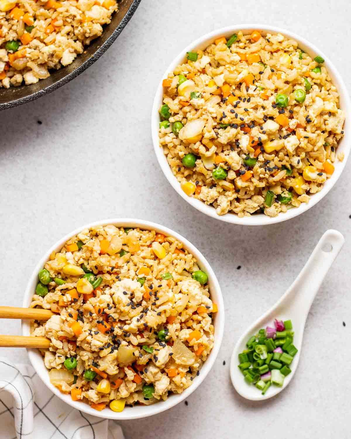 2 bowls of fried rice with chopped scallions and a skillet in the background.