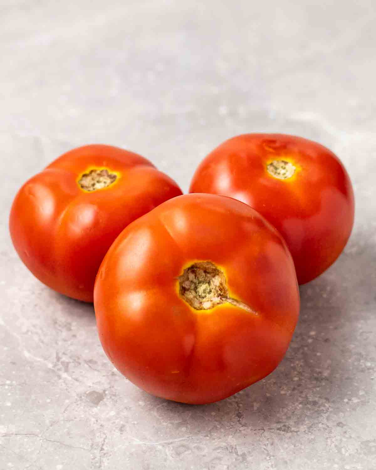 3 tomatoes arranged on a grey background.