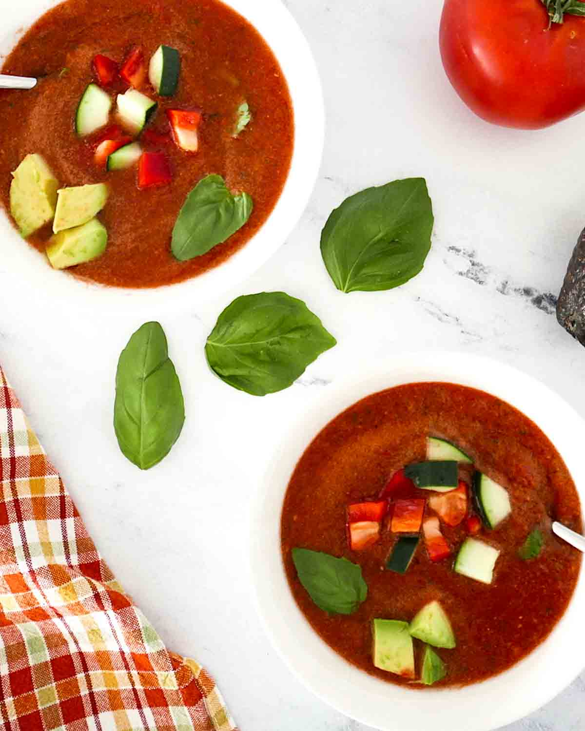 2 bowls of gazpacho with spoons topped with cucumber and tomato cubes. There are some basil leaves in the background.