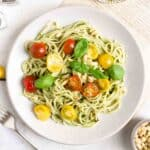 Pesto pasta served with cherry tomatoes on a white plate.