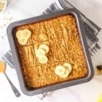 Banana oatmeal bars in square baking pan topped with sliced bananas drizzled with peanut butter.