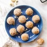 Coconut bliss balls arranged on a blue plate with cashews and more bliss balls in the background.