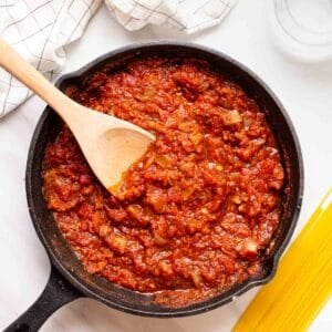 Marinara sauce in skillet with stirrer. There is some spaghetti and glass of water beside.