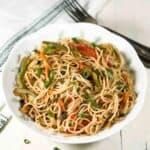 Hakka noodles in a white bowl.