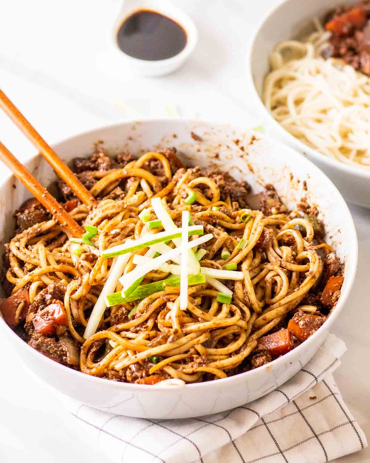 Jajangmyeon in a deep dish with a pair of chopsticks topped with sliced cucumber.