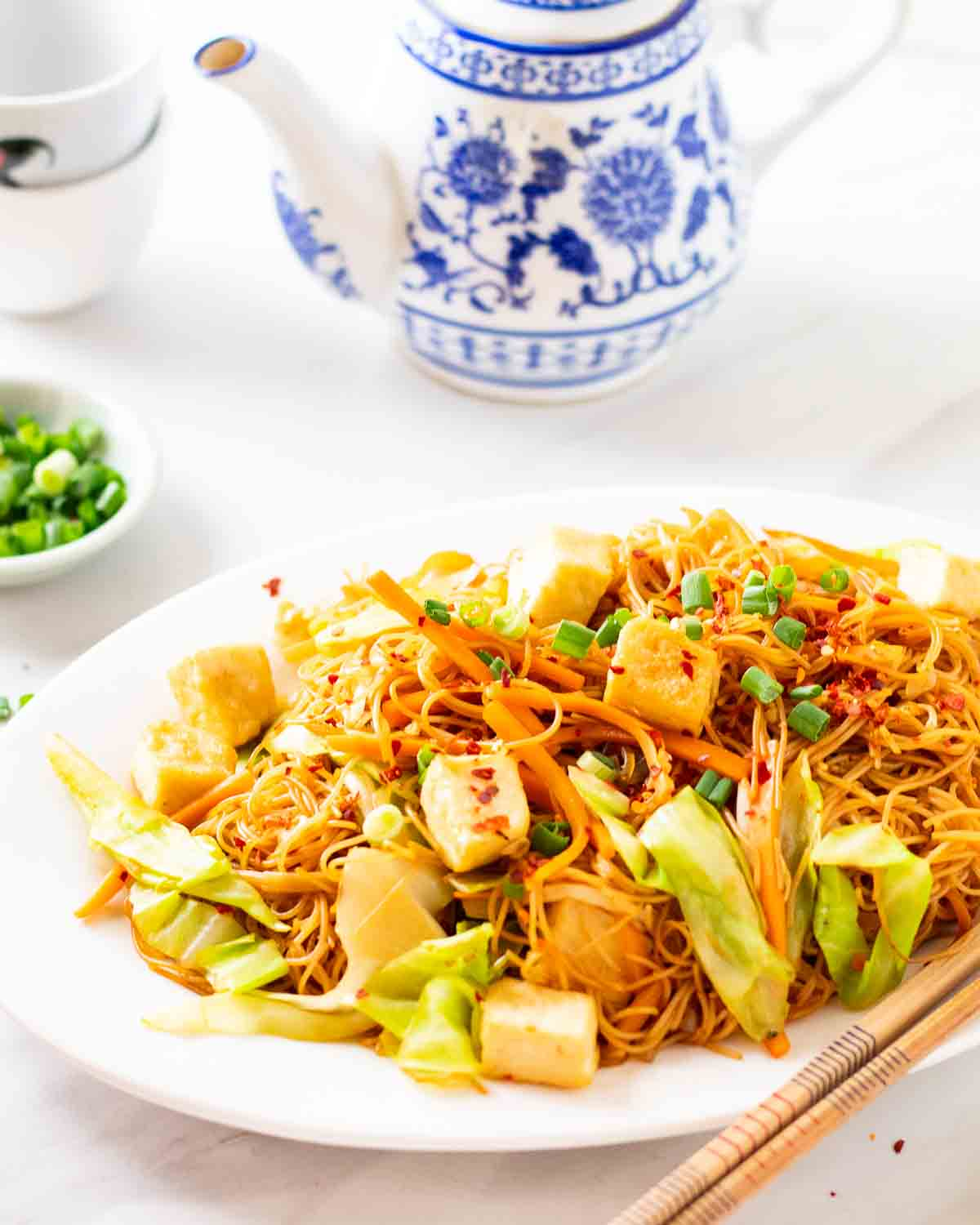 Stir-fry vermicelli on a white plate. There is a teapot, teacups and scallion behind.