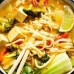 A close up of noodle soup with a pair of chopsticks.