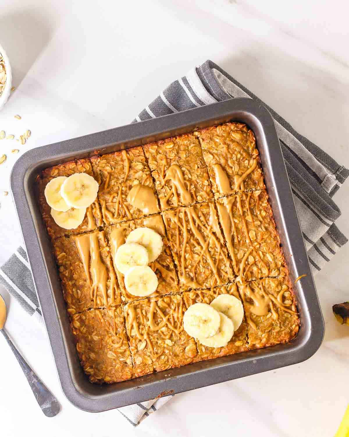 A tray of banana oatmeal bars topped with peanut butter and banana slices.