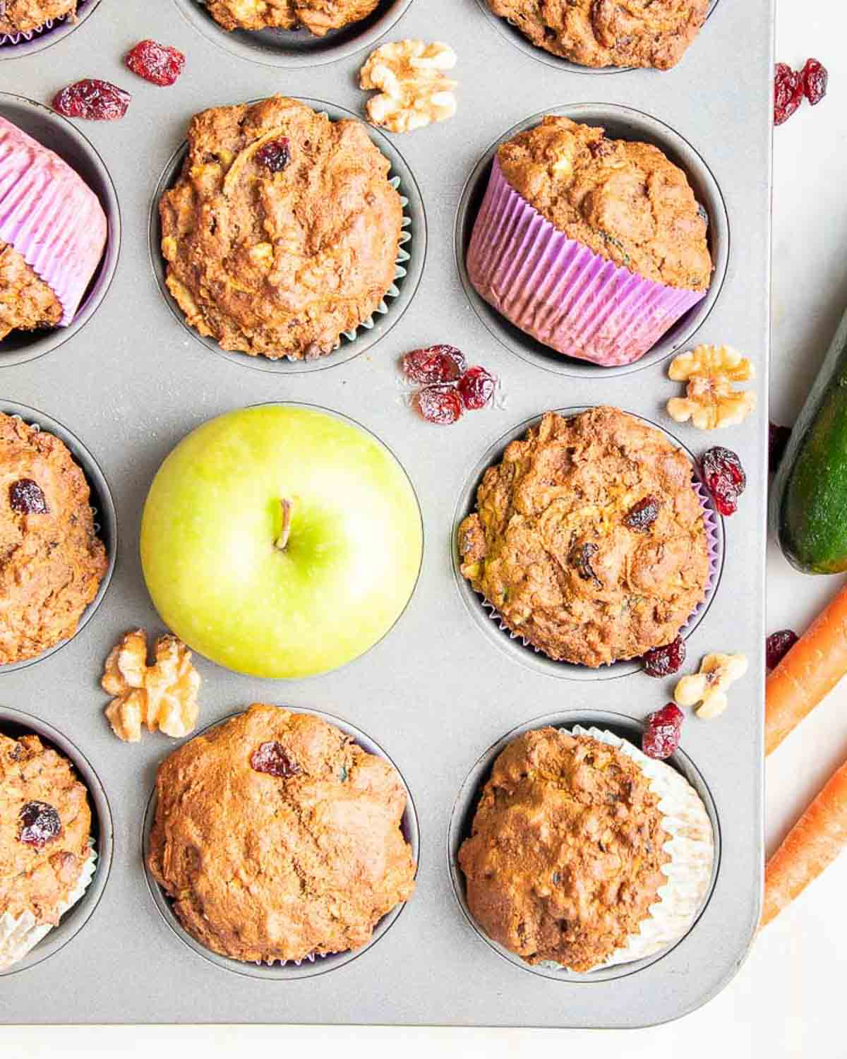 A tray of muffins with a green apple in the middles and carrots and zucchini beside the tray.