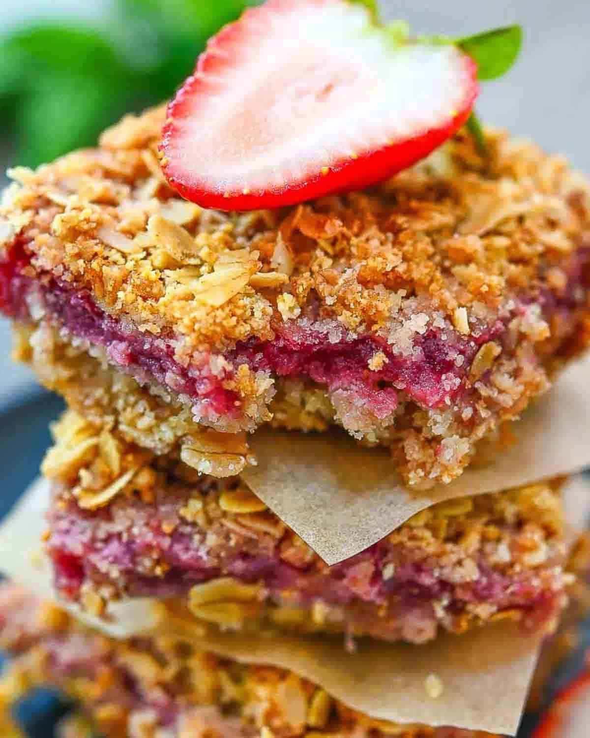 3 oatmeal bars stacked on top with each other with wax paper in between and half a strawberry on top.