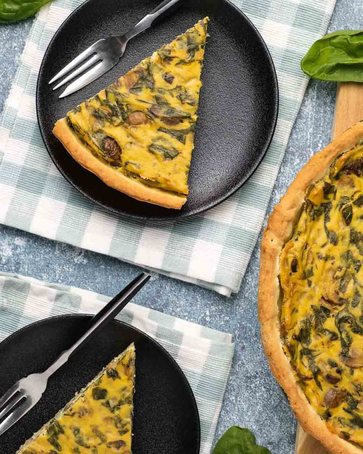 Slices of quiche served on 2 plate with forks.