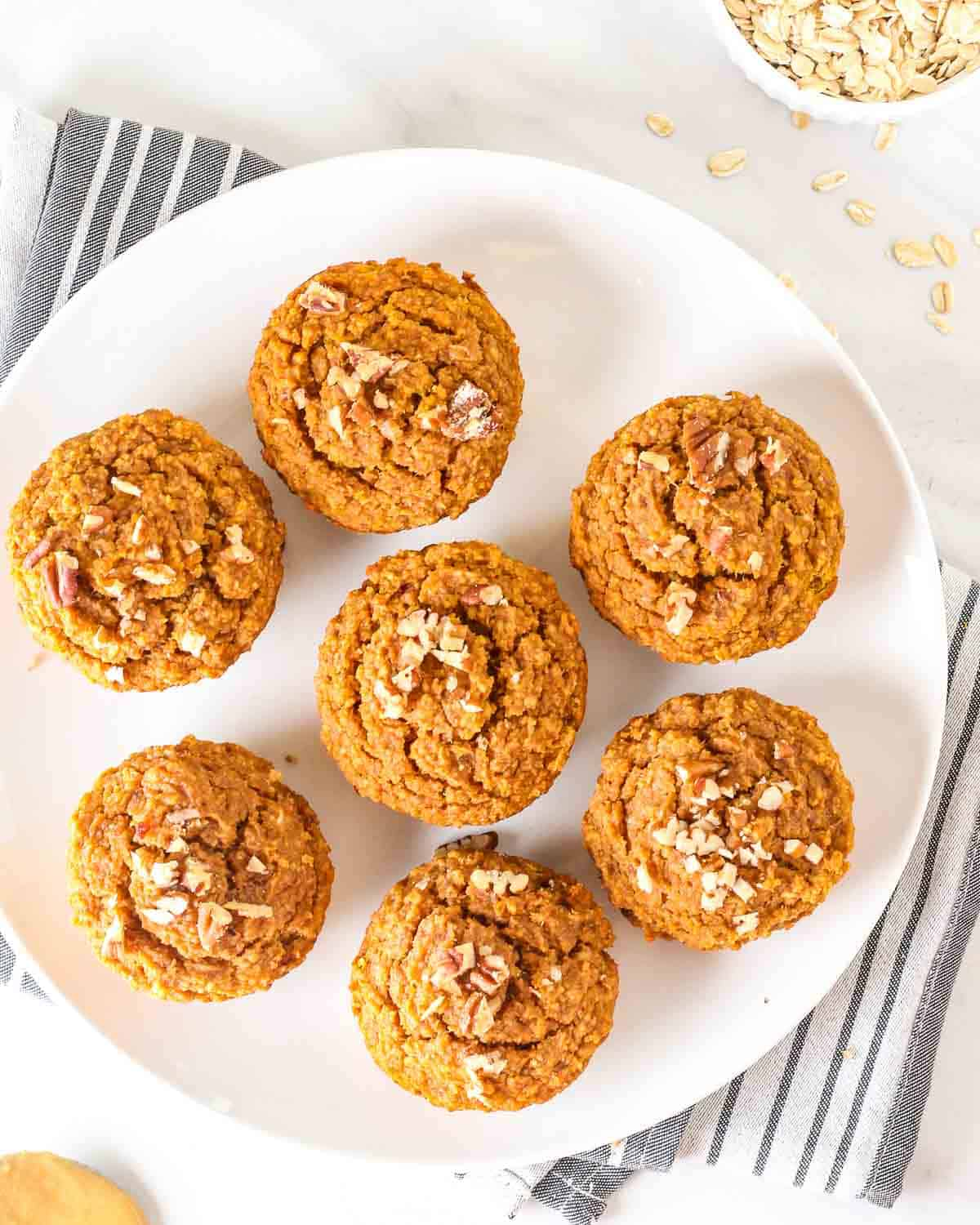 7 sweet potato muffins on a white plate on a table cloth.