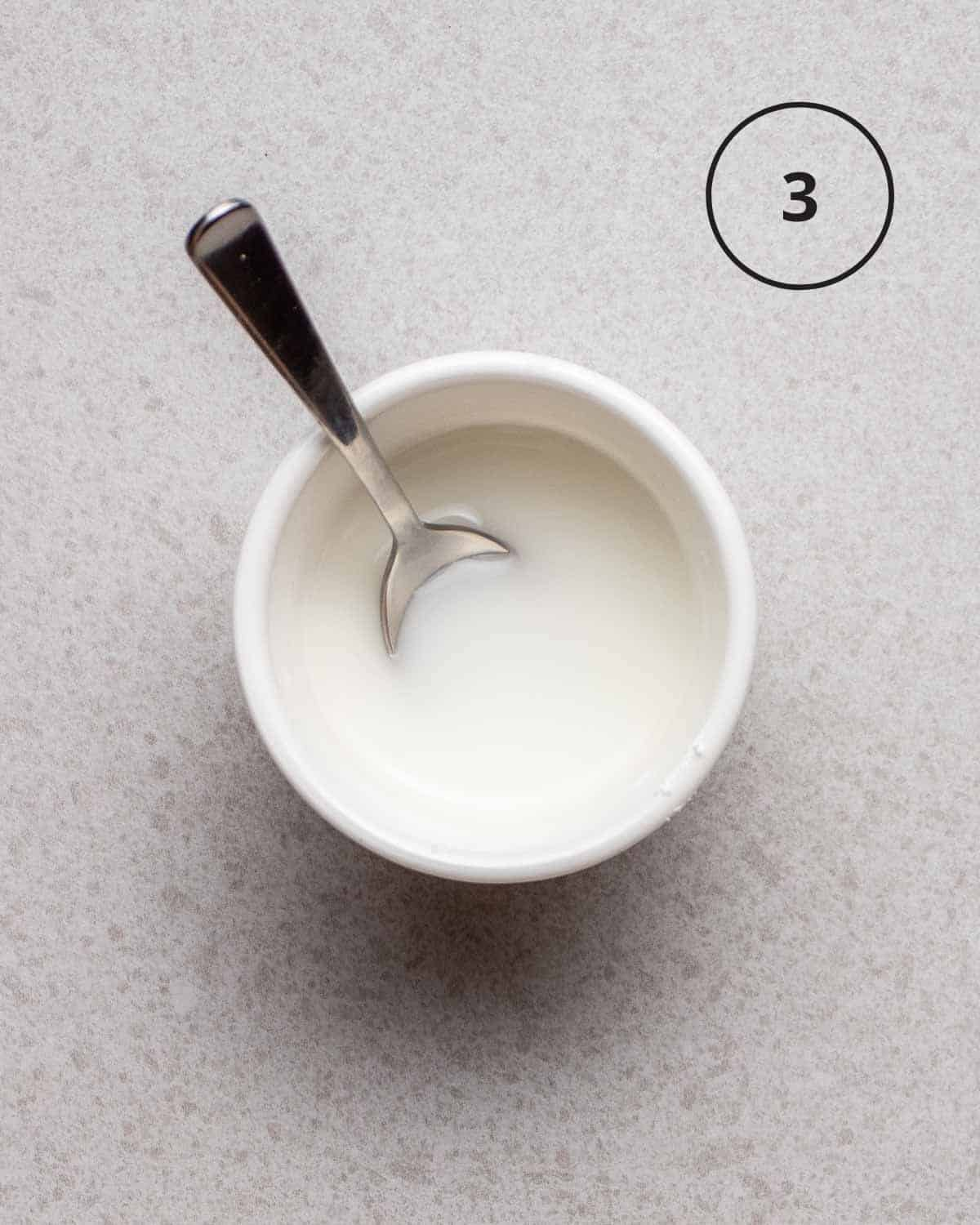 Cornstarch slurry in a white bowl with a spoon.