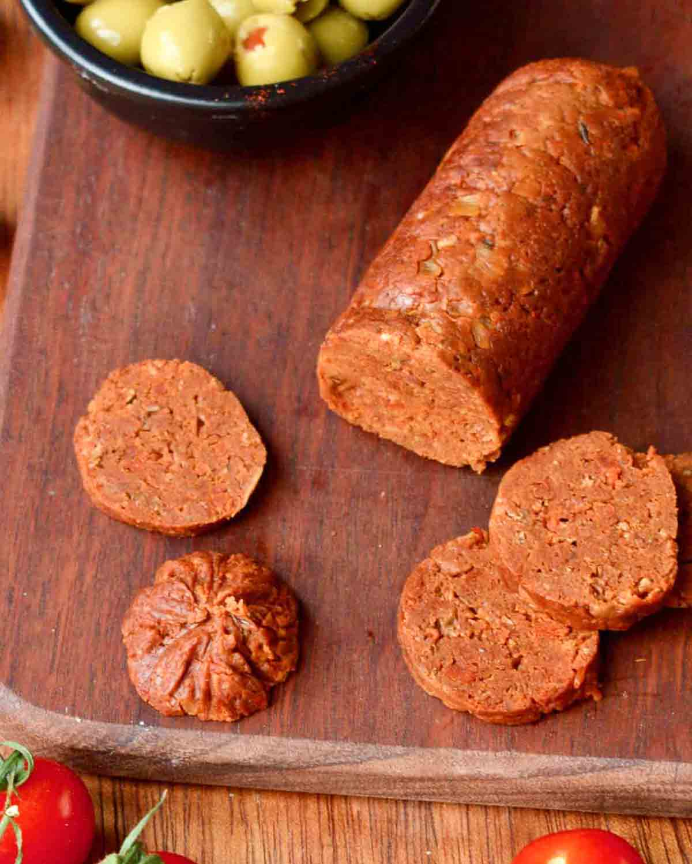 Partly sliced vegan chorizo on a chopping board.