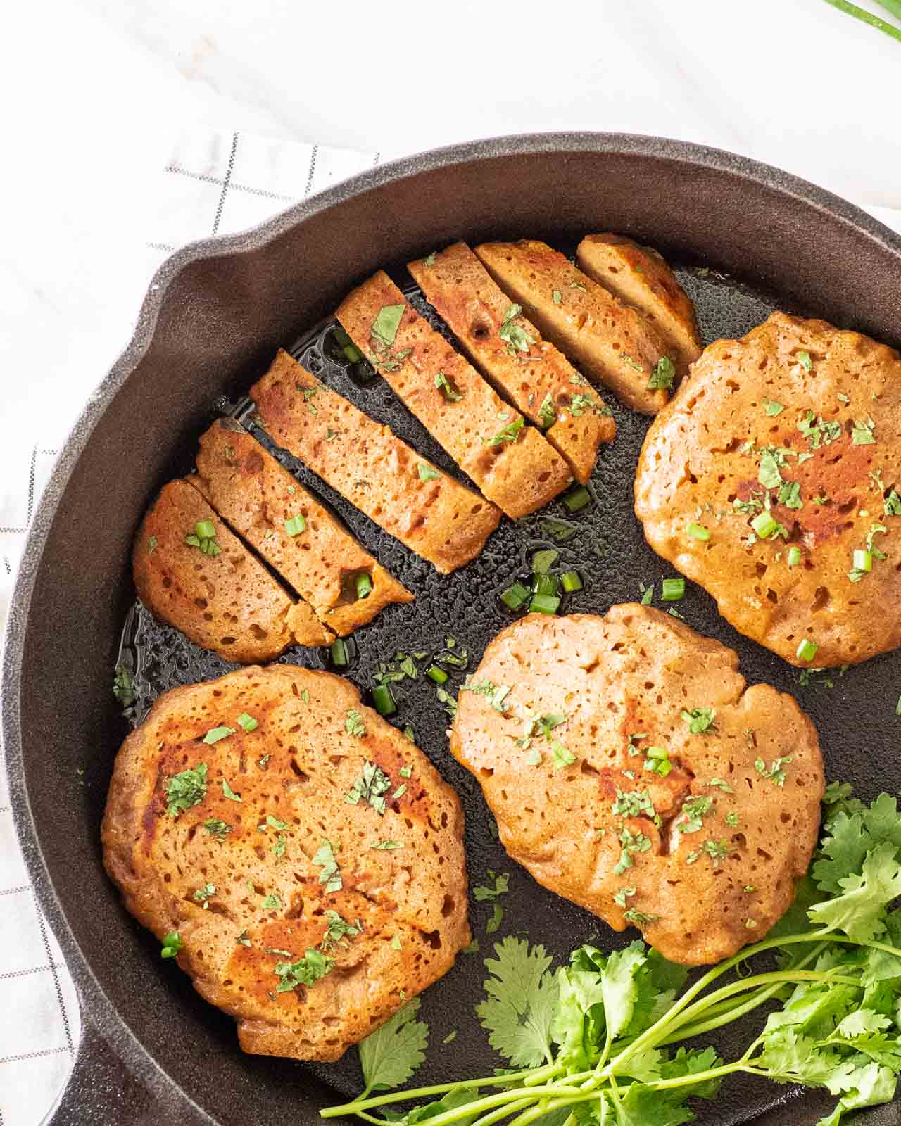 A few breasts of seitan chicken in a black pan topped with chopped cilantro.