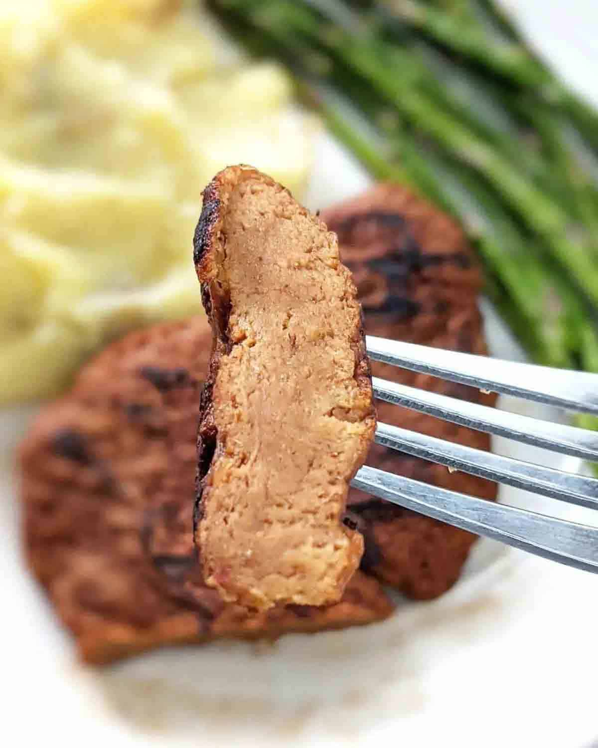 Fork holding a slice of vegan steak. There is a plate with steak, mashed potatoes and asparagus in the background.