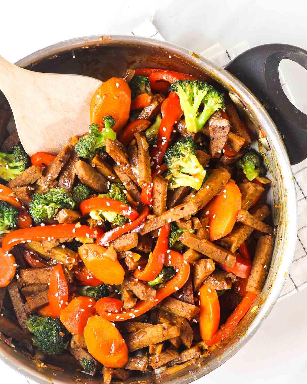 Seitan stir-fry in a pan with a wooden stirrer.