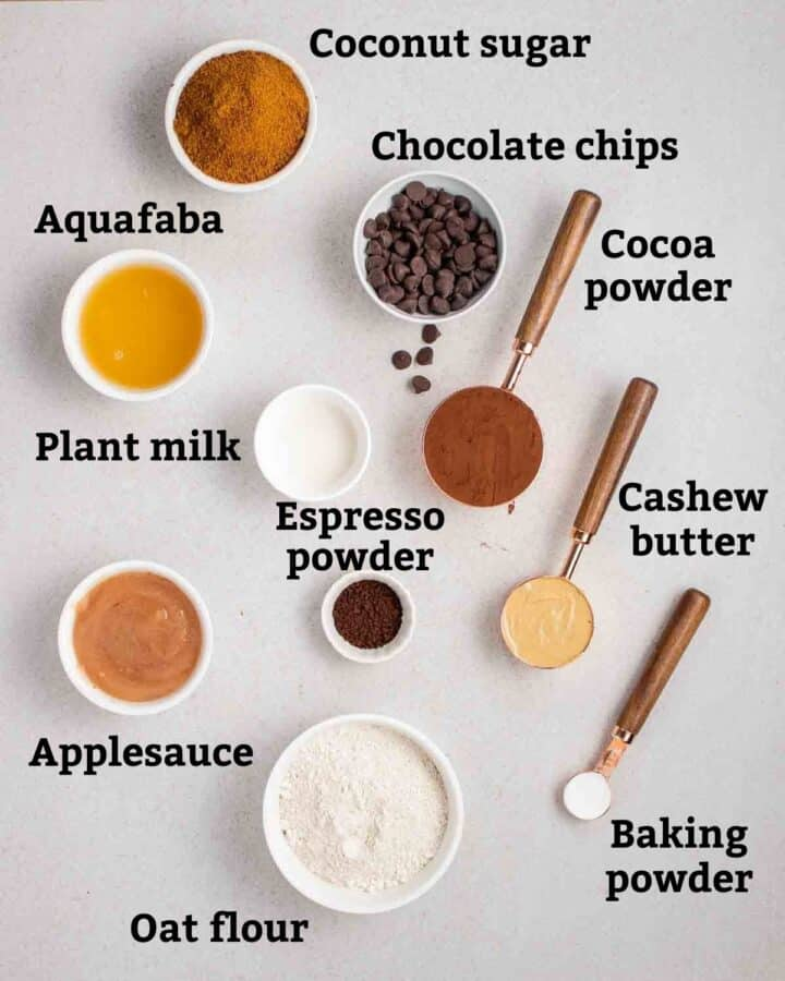 Ingredients needed like aquafaba, oat flour, cocoa powder, and applesauce on a grey background.
