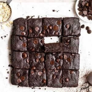 Tray of brownies on a parchment paper with dish of chocolate chips and cup of oats beside.