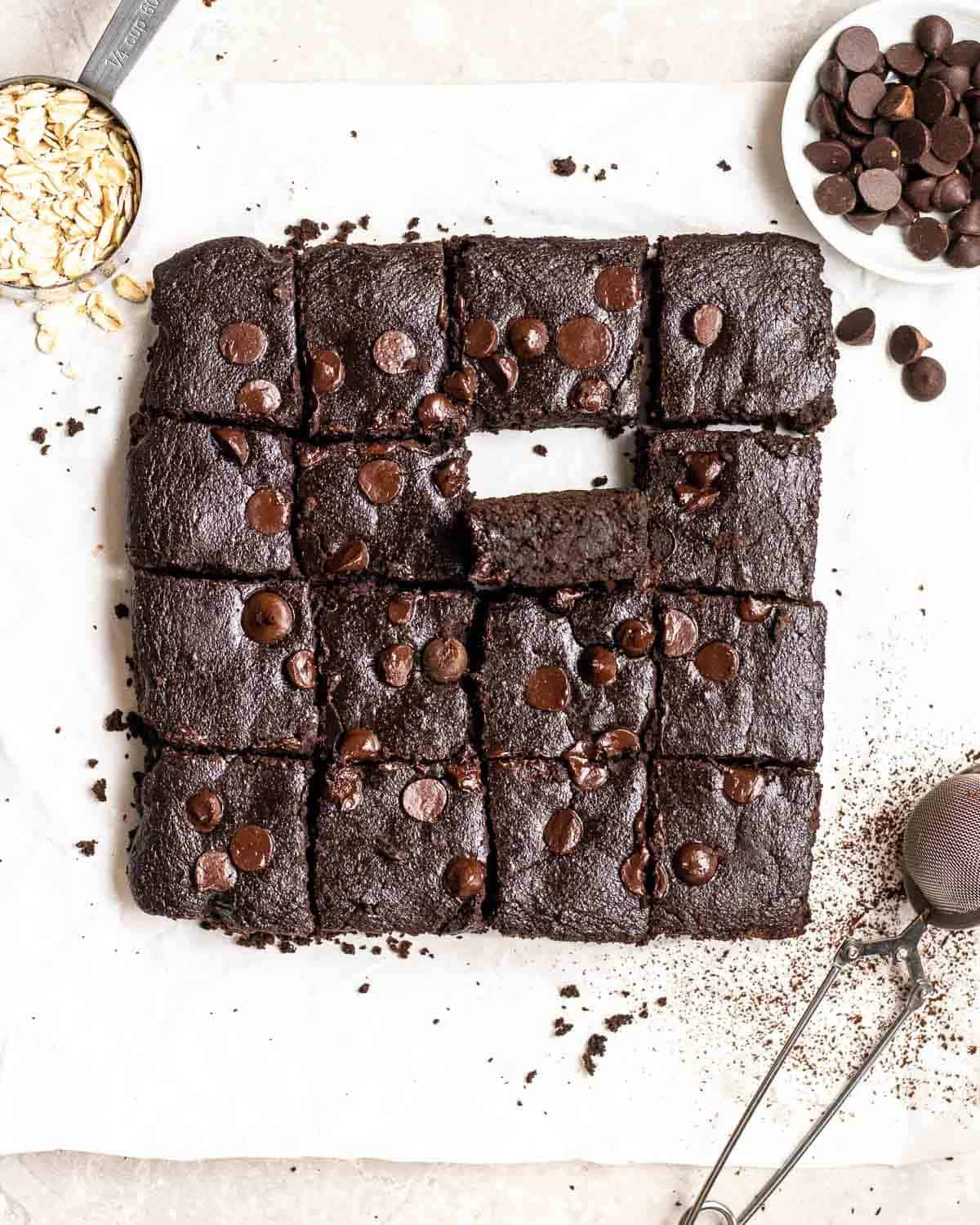 A tray of brownies on a parchment paper with chocolate chips, oats and a small colander beside.