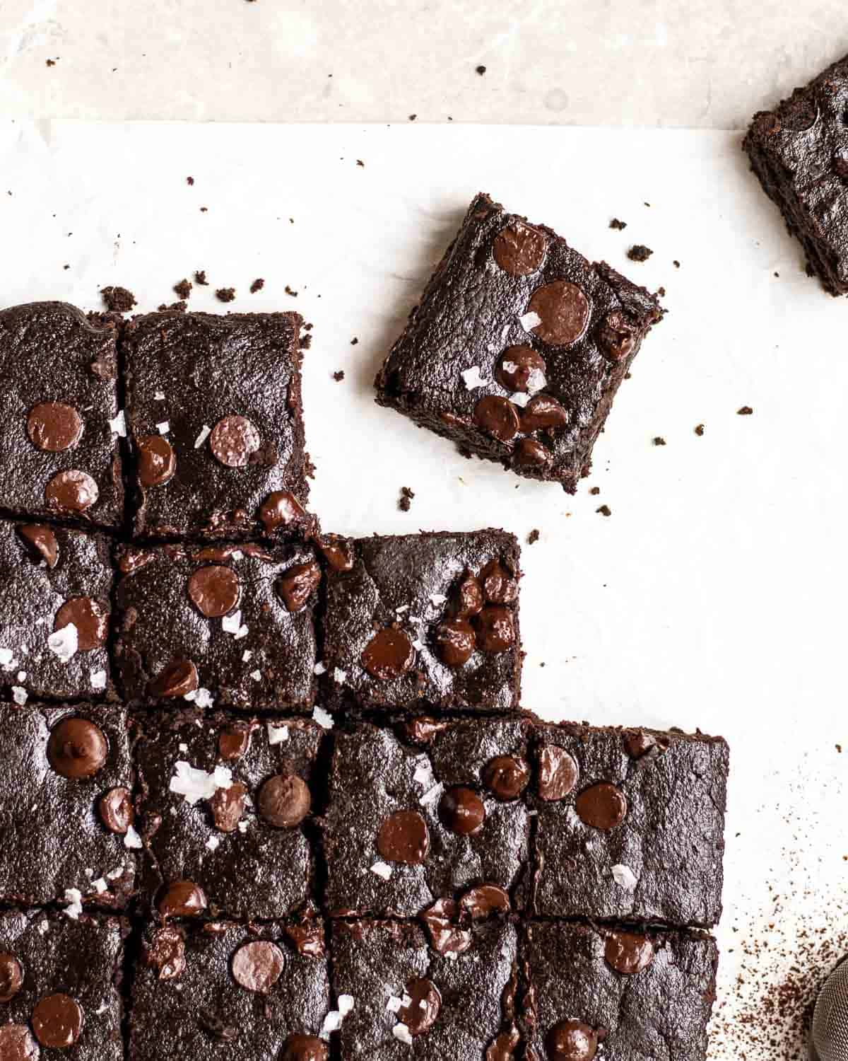 A tray of brownies arranged on a parchment paper topped with sea salt flakes.
