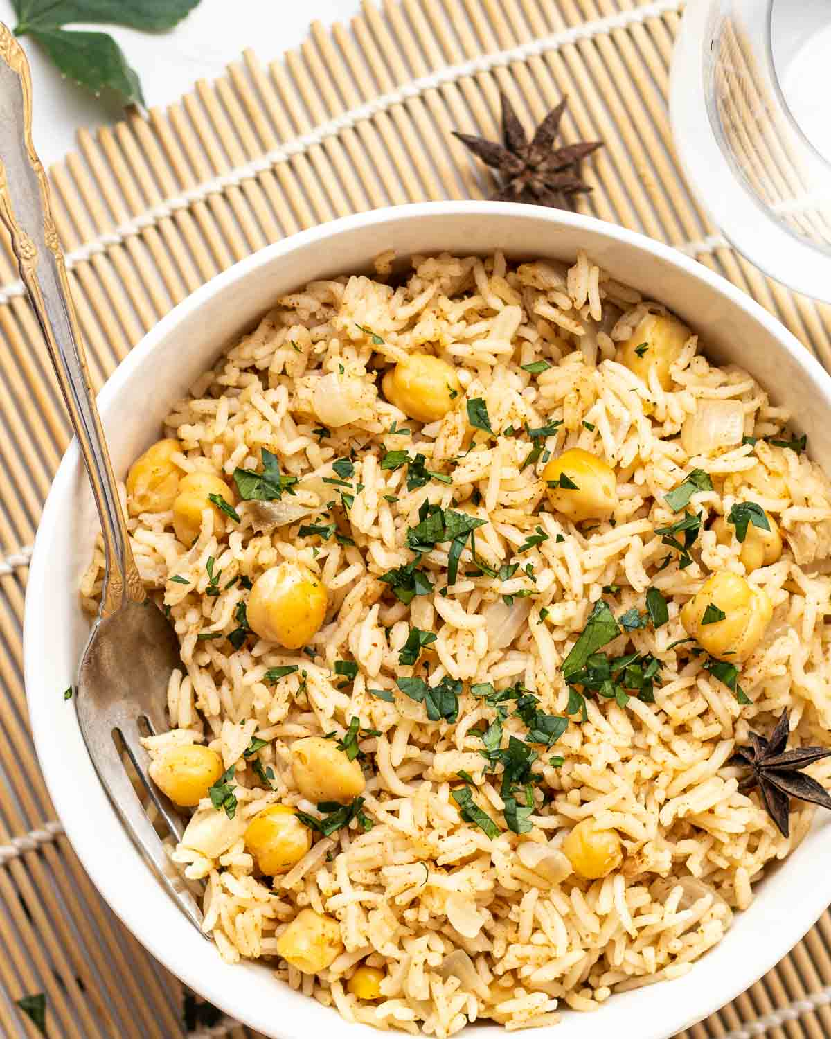 Chana pulao in a white bowl with a fork topped with chopped cilantro.