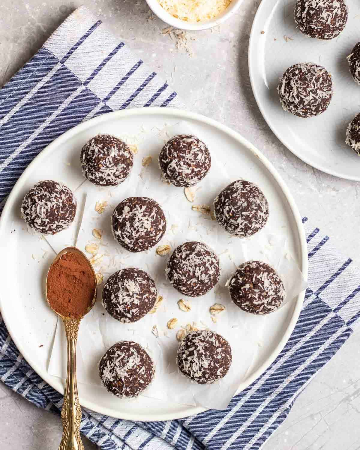 Protein balls arranged on a white plate with a spoonful of cocoa powder beside.