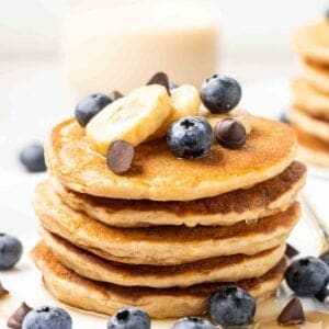Stack of vegan protein pancakes topped with banana slices, blueberries and chocolate chips with a glass of milk behind it.
