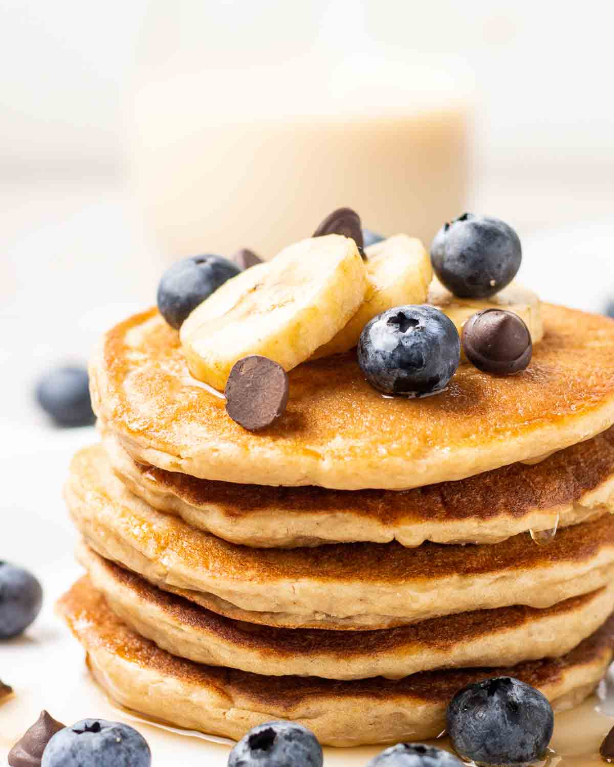 A stack of eggless protein pancakes topped with banana slices, blueberries and chocolate chips.