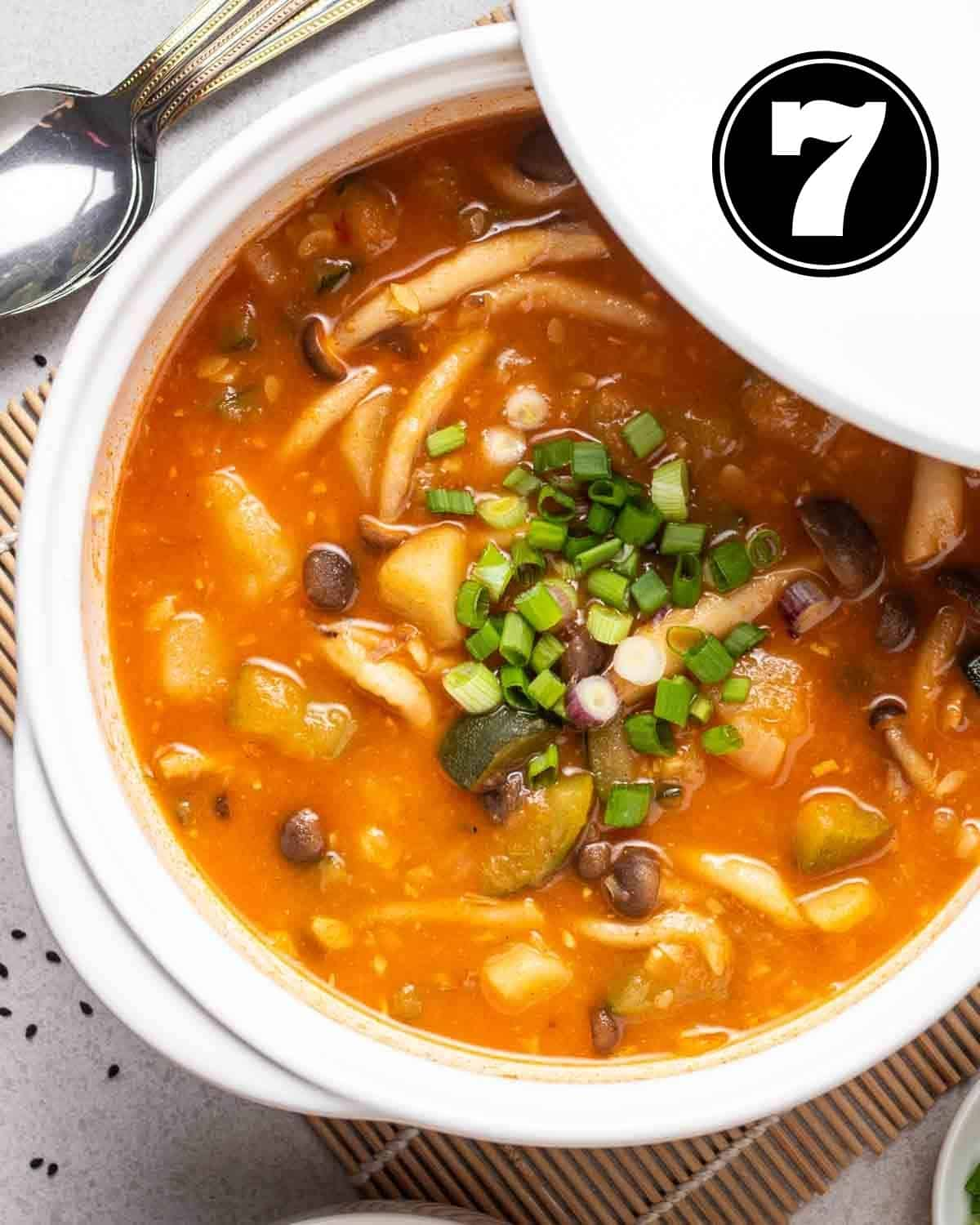 Gochujang soup in pot topped with chopped scallions.