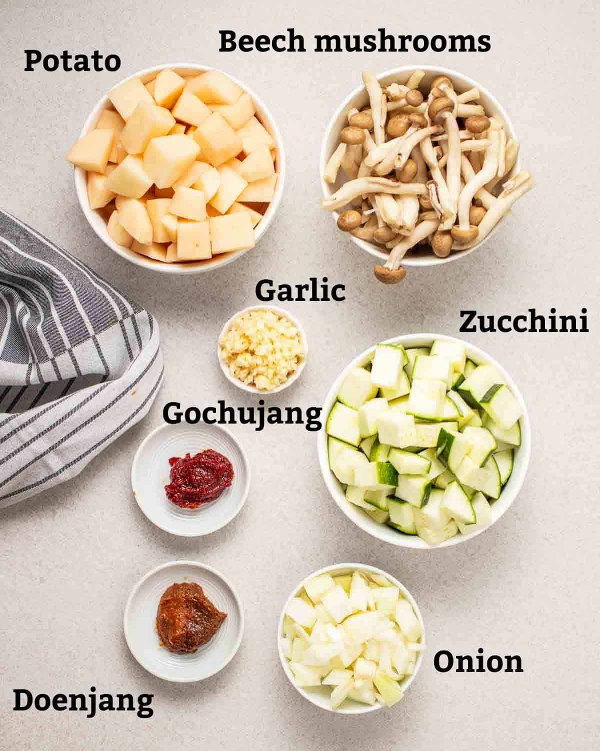 Ingredients needed like gochujang, doenjang, onion, garlic and vegetables on a grey background.